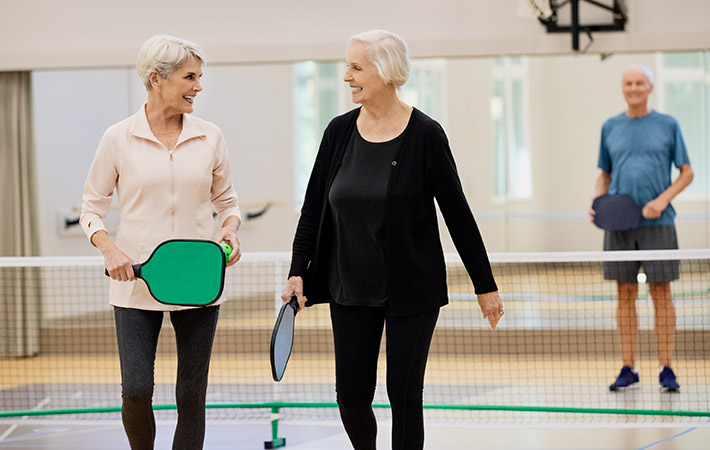 two ladies walking away from a man on a pickleball court